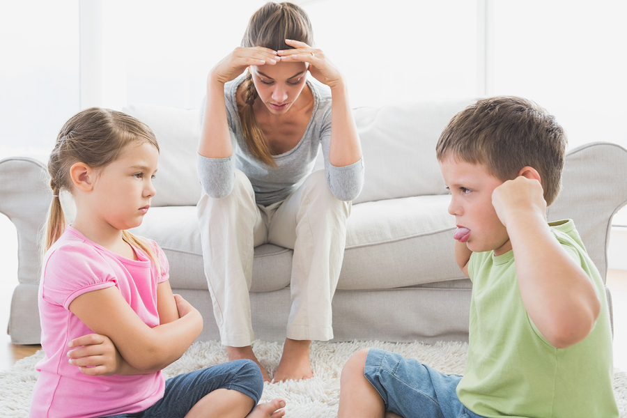 Fed up mother listening to her young children fight at home in t