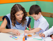 Little boy painting while teacher assisting him at classroom desk