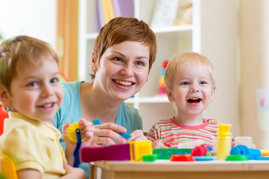 woman teaches children handcraft at kindergarten or playschool or home