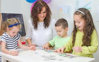 Young teacher plays with children in kindergarten.