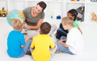 preschool teacher showing children countries on globe