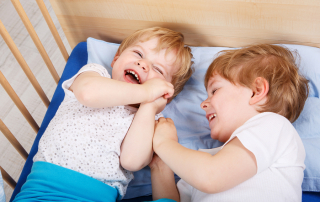 Two little toddler boys having fun and fighting together in bed before sleeping indoors