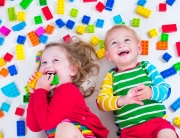 40332990 - child playing with colorful toys. little girl and baby boy with educational toy blocks. children play at day care or preschool. mess in kids room. view from above.