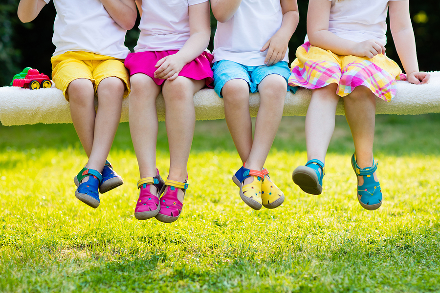 Footwear for children. Group of preschool kids wearing colorful leather shoes. Sandal summer shoe for young child and baby. Preschooler playing outdoor. Child clothing foot wear and fashion.