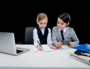 Children working with documents at workplace on black