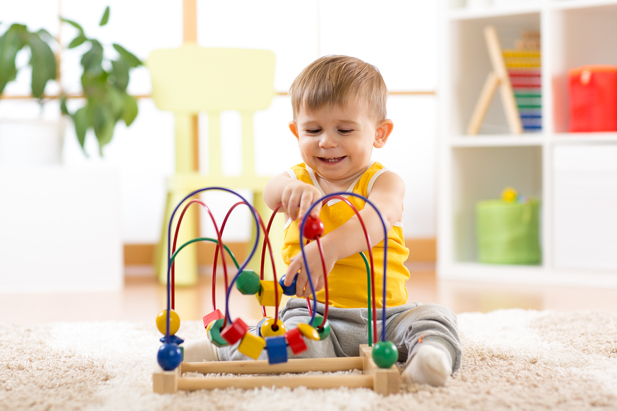 Happy kid boy plays with educational toy indoors