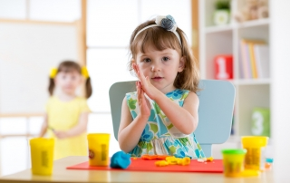Preschooler girl having fun together with colorful modeling clay at a daycare. Creative kid toddler molding at home. Children play in kindergarten.